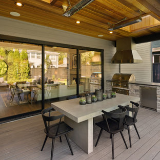 Inspiration for a large cottage backyard outdoor kitchen deck remodel in Seattle with a roof extension