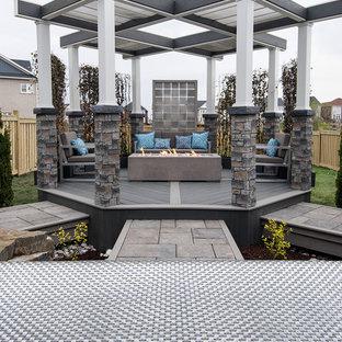 Idee per una terrazza industriale di medie dimensioni e dietro casa con un focolare e una pergola