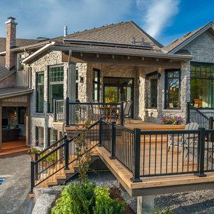 Esempio di una grande terrazza american style dietro casa con un focolare e un tetto a sbalzo