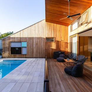 This is an example of a large modern deck in Gold Coast - Tweed with a roof extension.