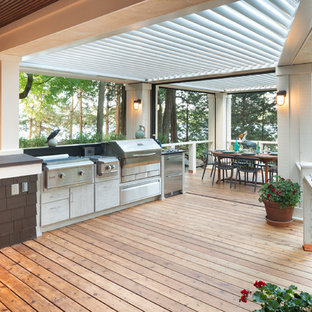 Large coastal backyard outdoor kitchen deck photo in Minneapolis with a pergola