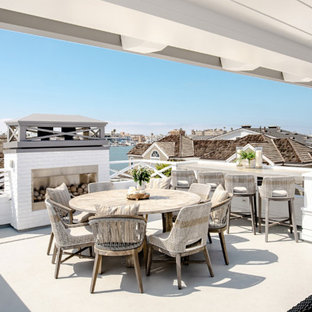 Deck - large coastal rooftop deck idea in Orange County with a fireplace and a roof extension