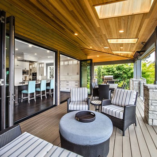 Large transitional backyard outdoor kitchen deck photo in Seattle with a roof extension