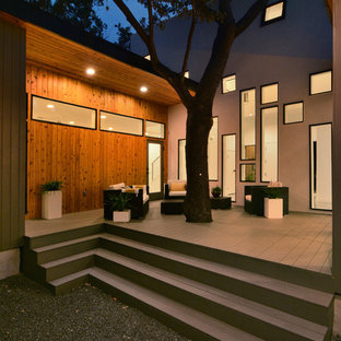 Inspiration for a mid-sized modern backyard deck remodel in Austin with a roof extension