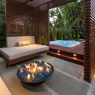 Photo of a small contemporary backyard deck in Los Angeles with a fire feature and a pergola.