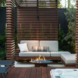 Small trendy backyard deck photo in Los Angeles with a fire pit and a pergola