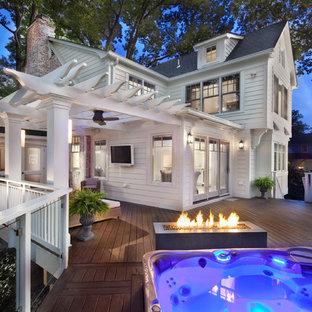 Cette photo montre une grande terrasse et balcon arrière chic avec un foyer extérieur et une pergola.