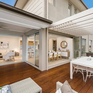 Photo of a large beach style backyard deck in Sydney with an outdoor kitchen and a roof extension.