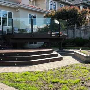 This is an example of a large modern backyard deck in Vancouver with no cover.