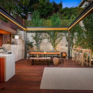 This is an example of a mid-sized contemporary backyard deck in Melbourne with an outdoor kitchen and no cover.