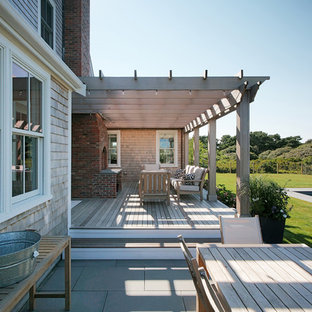 Design ideas for a beach style backyard deck in Boston with a fire feature and a pergola.