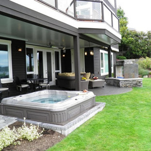This is an example of a large traditional backyard deck in Seattle with a roof extension and a fire feature.