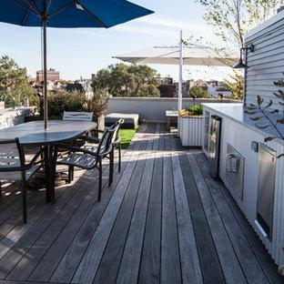 Idee per una terrazza industriale di medie dimensioni e sul tetto con un giardino in vaso e un parasole