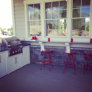 Large farmhouse backyard outdoor kitchen deck photo in Salt Lake City with a roof extension
