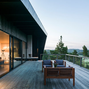 Deck - large scandinavian backyard deck idea in Gothenburg with a fire pit and a roof extension
