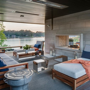 Inspiration for a large modern backyard deck remodel in Other with a roof extension and a fire pit