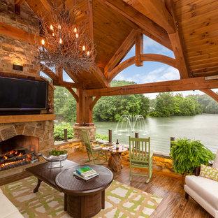 Cette image montre une terrasse arrière chalet avec une cheminée et une pergola.