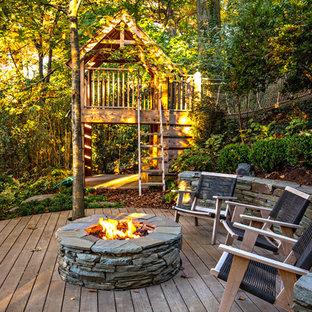 Inspiration pour une terrasse arrière chalet avec un foyer extérieur.