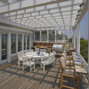 Idee per grandi terrazze e balconi stile marinaro dietro casa con una pergola