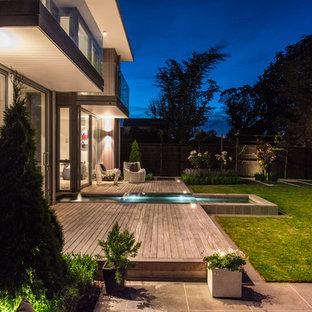 Diseño de terraza actual, en patio trasero, con fuente