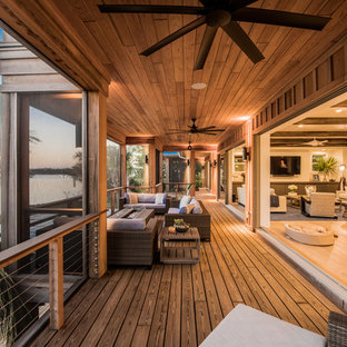 Deck - tropical deck idea in Tampa with a fire pit and a roof extension