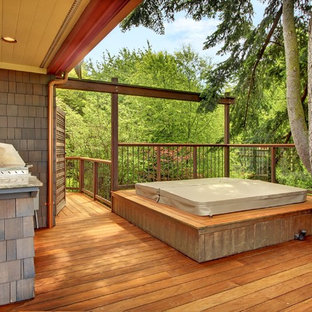 Example of an arts and crafts outdoor kitchen deck design in Seattle with a roof extension
