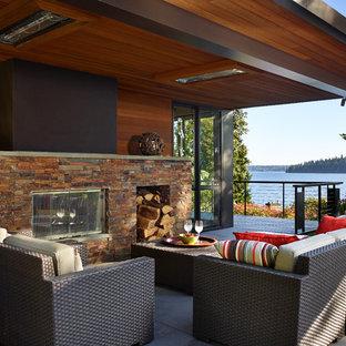 Ispirazione per terrazze e balconi minimal di medie dimensioni e dietro casa con un tetto a sbalzo e un caminetto