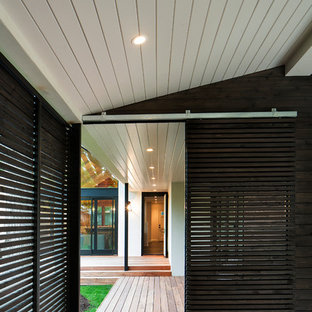 Example of a mid-sized transitional backyard deck design in Austin with a roof extension
