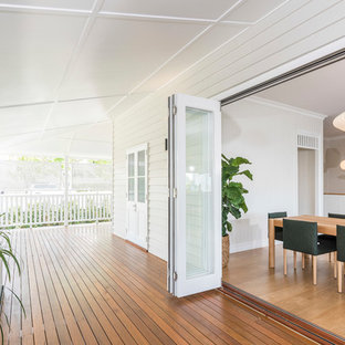 Transitional backyard deck in Brisbane with a roof extension.
