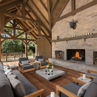 Deck - country backyard deck idea in Cleveland with a fireplace and a roof extension