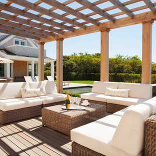 Traditional backyard deck in Providence with a pergola.