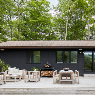 Large danish backyard deck photo in New York with a roof extension