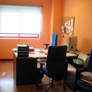 Inspiration för stora moderna hemmabibliotek, med orange väggar, mellanmörkt trägolv, ett fristående skrivbord och brunt golv