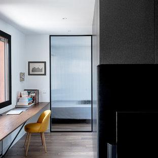 Ejemplo de estudio minimalista, de tamaño medio, sin chimenea, con paredes blancas, suelo de madera en tonos medios, suelo marrón y escritorio empotrado
