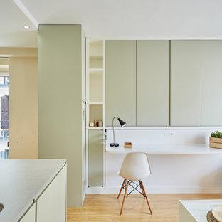 Ejemplo de despacho actual, de tamaño medio, sin chimenea, con escritorio empotrado y suelo de madera clara