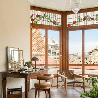 Imagen de despacho mediterráneo, de tamaño medio, con paredes beige, suelo de madera oscura, suelo marrón y escritorio independiente
