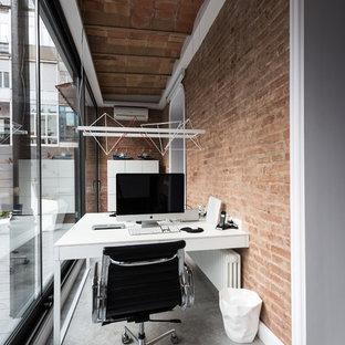 Idée de décoration pour un petit bureau urbain avec béton au sol, un bureau intégré, un mur orange et aucune cheminée.