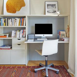 Inspiration för ett litet funkis hemmabibliotek, med beige väggar, ett inbyggt skrivbord, mellanmörkt trägolv och orange golv