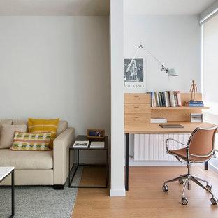 Foto de despacho nórdico con suelo de madera en tonos medios, paredes blancas y suelo marrón