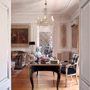 Imagen de despacho clásico, grande, con paredes multicolor, suelo de madera en tonos medios y escritorio independiente