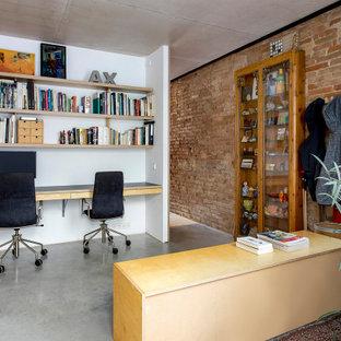 На фото: рабочее место среднего размера в стиле лофт с белыми стенами, бетонным полом, встроенным рабочим столом, серым полом и кирпичными стенами с