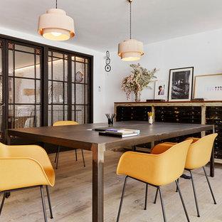 Imagen de estudio urbano, sin chimenea, con paredes blancas, suelo de madera clara y escritorio independiente