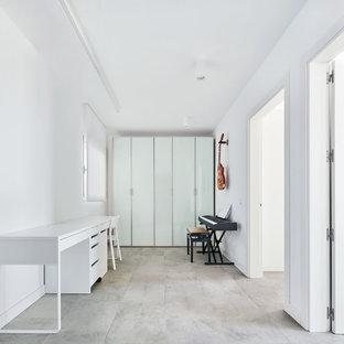 Foto de estudio contemporáneo con paredes blancas, escritorio independiente y suelo gris