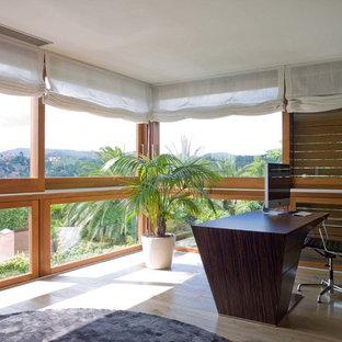 Exotisk inredning av ett mellanstort hemmabibliotek, med ljust trägolv och ett fristående skrivbord