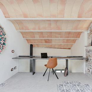 Modelo de despacho mediterráneo, de tamaño medio, sin chimenea, con paredes blancas, suelo de cemento, escritorio empotrado y suelo gris