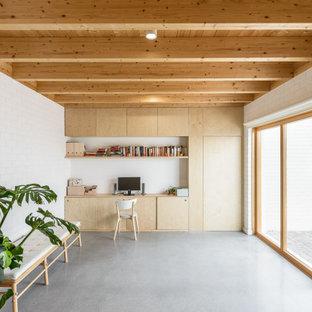 Свежая идея для дизайна: большое рабочее место в современном стиле с белыми стенами, кирпичным полом, встроенным рабочим столом, серым полом, деревянным потолком и кирпичными стенами - отличное фото интерьера