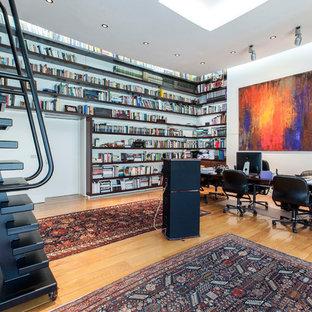 Imagen de despacho actual con paredes blancas, suelo de madera en tonos medios, escritorio independiente y suelo marrón