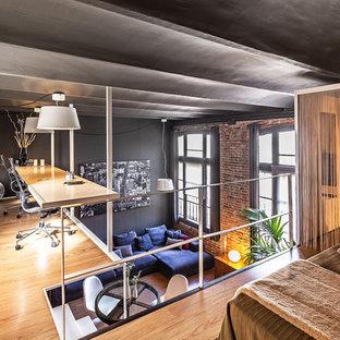 Diseño de despacho contemporáneo con paredes grises, suelo de madera clara, escritorio empotrado y suelo beige