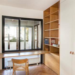 Imagen de despacho actual, sin chimenea, con paredes blancas, suelo de madera en tonos medios, escritorio empotrado y suelo marrón