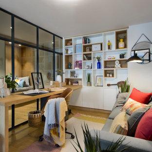 Imagen de despacho actual con paredes blancas, suelo de madera en tonos medios, escritorio empotrado y suelo marrón